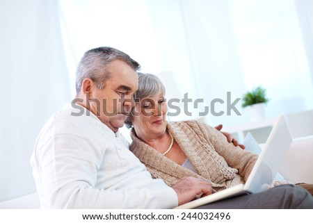 Couple of seniors networking at home - stock photo