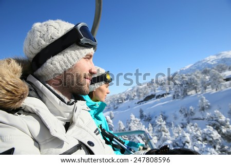 Couple of skiers going up ski slope with chairlift - stock photo