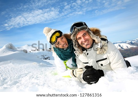 Couple of skiers laying down in the snow - stock photo