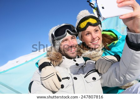 Couple of skiers making selfy with smartphone - stock photo
