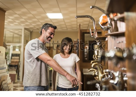 Couple of smiling adults choosing bathroom faucets in plumbing store