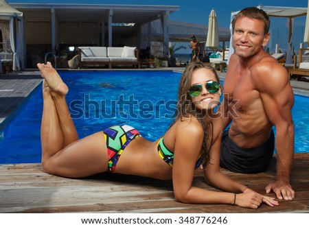Couple of smiling muscular man and woman in sunglasses and swimwear near blue swimming pool. - stock photo