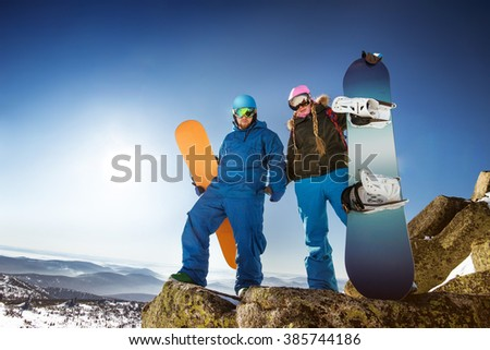 Couple of snowboarders stands on backdrop of mountains and valley. Sheregesh resort, Siberia, Russia - stock photo