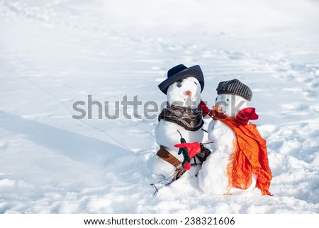 Couple of snowmen taking hand of each other and dancing - stock photo