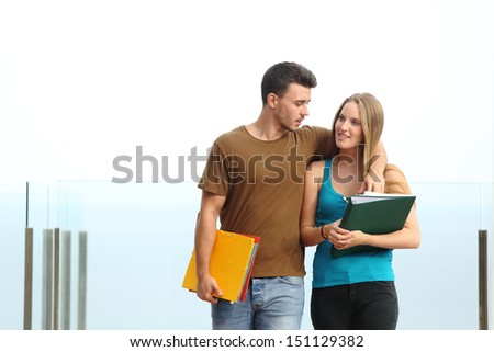 Couple of students walking towards camera outdoor with a white background - stock photo