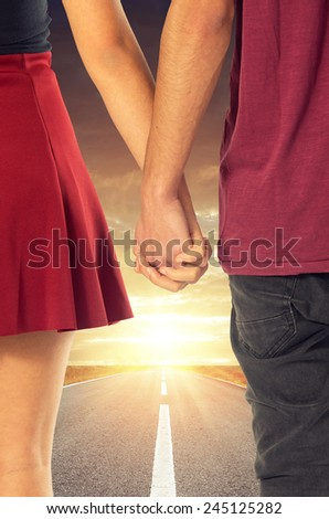 Couple of sweethearts holding hands and walking together in a road into the sun - stock photo