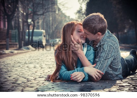 Couple of teenagers lying in street together - stock photo