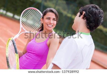 Couple of tennis players talking at the court