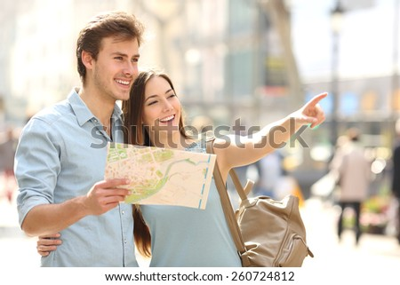 Couple of tourists consulting a city guide searching locations in the street and pointing - stock photo