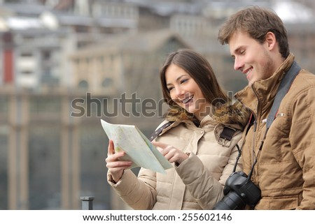 Couple of tourists consulting a guide in winter with an urban background - stock photo