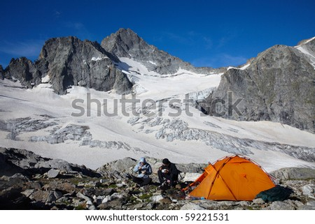 Couple of tourists having a breakfast near of tent - stock photo