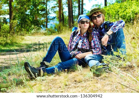 Couple of tourists having a rest on a trekking trail. - stock photo