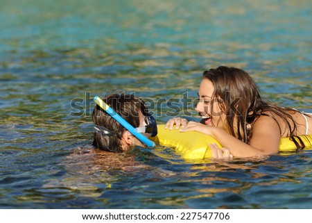 Couple of tourists laughing while bathing on a tropical beach with turquoise water on summer vacations - stock photo