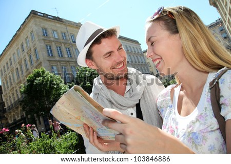 Couple of tourists looking at city tour map - stock photo