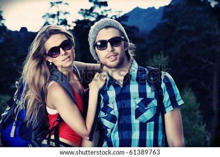 Couple of tourists making their journey at the mountains. - stock photo