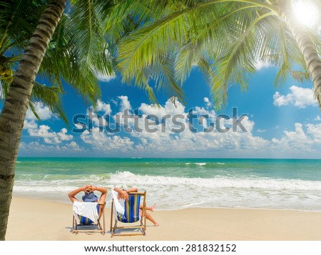 Couple of tourists on the beach in Thailand - stock photo