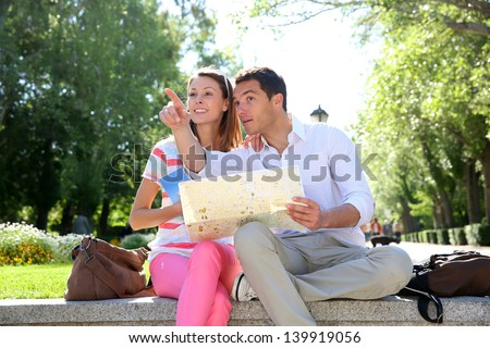 Couple of tourists relaxing in park - stock photo