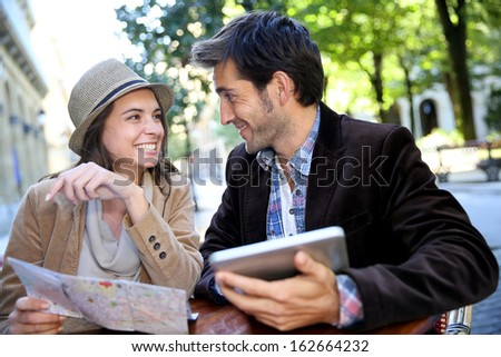 Couple of tourists sitting at coffee shop table - stock photo
