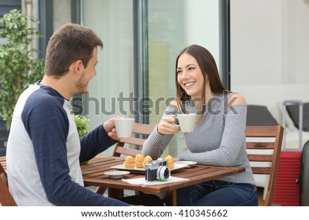 Couple of tourists sitting in a balcony table relaxing drinking and talking at hotel room on vacations - stock photo