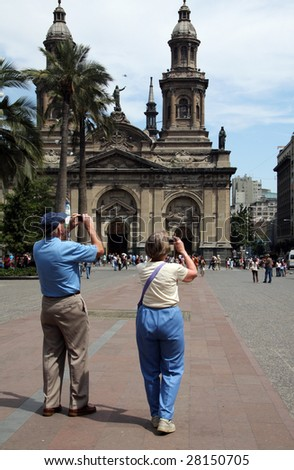 Couple of tourists taking pictures at Plaze de Armas in Santiago, Chile - stock photo