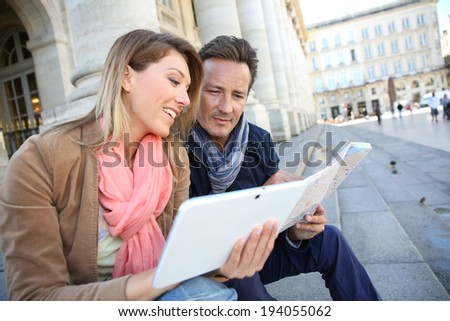 Couple of tourists using digital tablet in town - stock photo