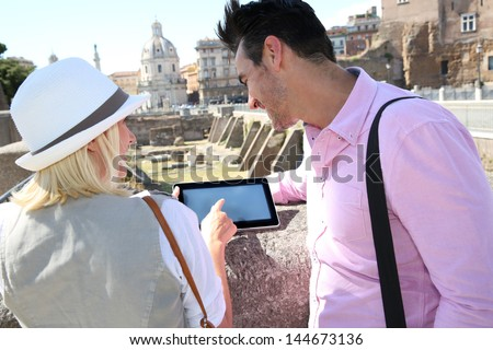 Couple of tourists using tablet to visit Rome Capital - stock photo