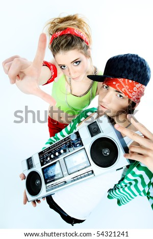 Couple of trendy teenagers posing together over black background. - stock photo