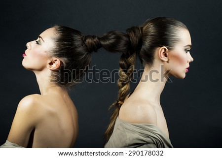 Couple of two undressed sexy pretty young women sitting back to back with beautiful brown woven hairdo on black background, horizontal picture - stock photo