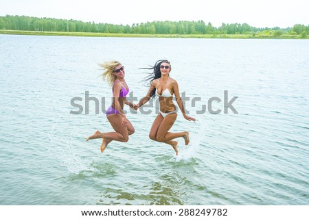 Couple of two woman jump In Water with splash Girls wear sexy bikini Female fly in air under wive texture against forest trees and sky background Empty space for inscription Sunglasses on faces  - stock photo