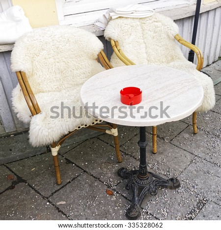Couple of wicker chairs covered with sheepskin and a table in front of the building in Garmisch-Partenkirchen. It is a mountain resort town in Bavaria, southern Germany, in the heart of the Alps - stock photo