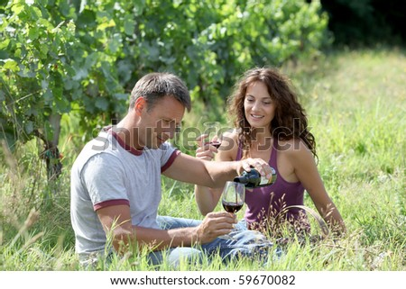 Couple of winegrowers drinking wine in vineyard - stock photo