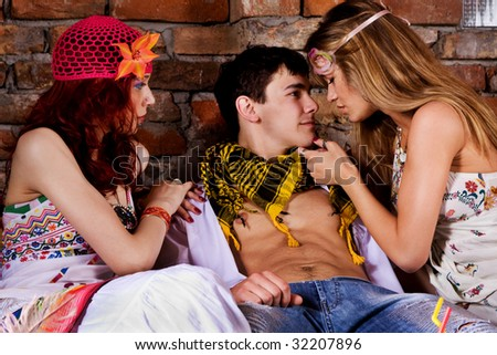 couple of women and man on a party flirting, indoor shot - stock photo