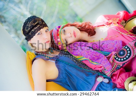 couple of women in oriental clothes sitting in garden - stock photo