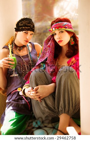 couple of women wearing colorful oriental  clothes enjoy in summer day - stock photo