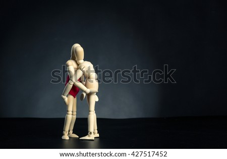 Couple of wooden figures hugging - stock photo