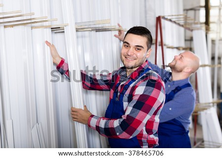 Couple of workmen in blue uniform inspecting window frames at factory - stock photo