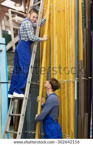 Couple of workmen inspecting window PVC at factory - stock photo