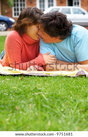 couple of young adults kissing outdoors on the grass - stock photo
