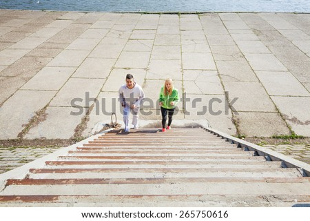 Couple of young athletes running up the stairs while exercising outdoors - stock photo
