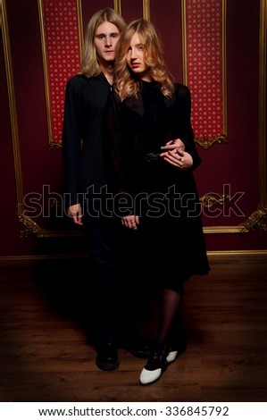 Couple of young blond people dressed in black in a dark gothic room - stock photo