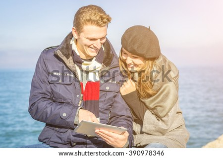 Couple of young caucasian lovers smiling using their tablet at the beach - stock photo