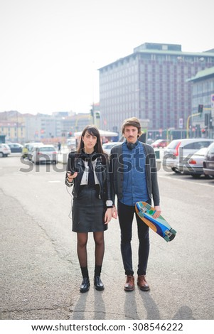 Couple of young caucasian woman and man with a skate and moustache posing trough the streets of the city listening to music by technological device - carefreeness, friendship, love, youth concept  - stock photo
