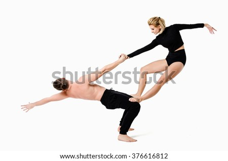 Couple of young dancers make acrobatic elements - stock photo