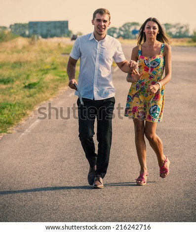 couple of young guys and girls walking on the road - stock photo