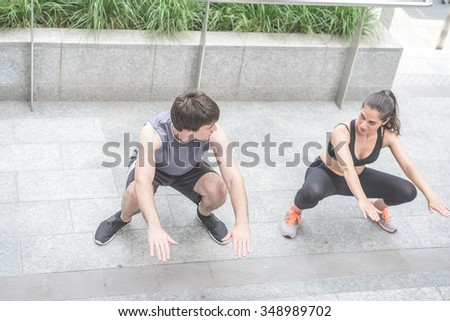 Couple of young handsome caucasian sportive man and woman doing squat, staring into each other's eyes - sportive, healthy, fitness concept - stock photo