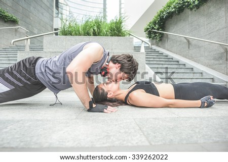 Couple of young handsome caucasian sportive man and woman stretching - he is doing push ups kissing her girlfriend, both with eyes closed - love, fitness, healthy concept  - stock photo