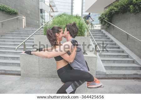 Couple of young handsome caucasian sportive man and woman stretching together - he is doing squt with her grasp on his chest - sportive, training, healthy concept  - stock photo