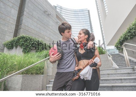 Couple of young handsome caucasian sportive man and woman walking downstairs, he is holding a basket ball, both starving into each other's eyes - relaxing, break, sportive concept - stock photo