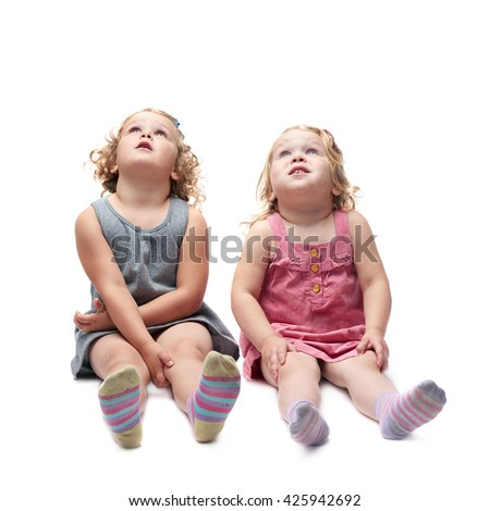 Couple of young little girls sisters with curly hair in gray and pink dress sitting over isolated white background - stock photo