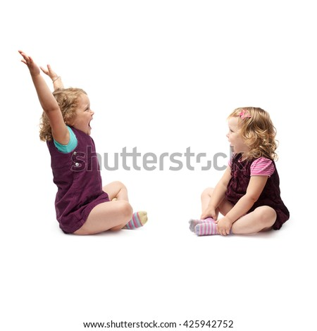 Couple of young little girls sisters with curly hair in purple dress sitting over isolated white background - stock photo